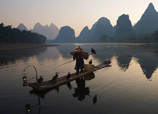 Cormorant fisherman on the Yulong river at dusk near Yangshou, Guangxi Province, China