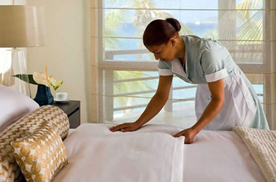Maid making up hotel bed