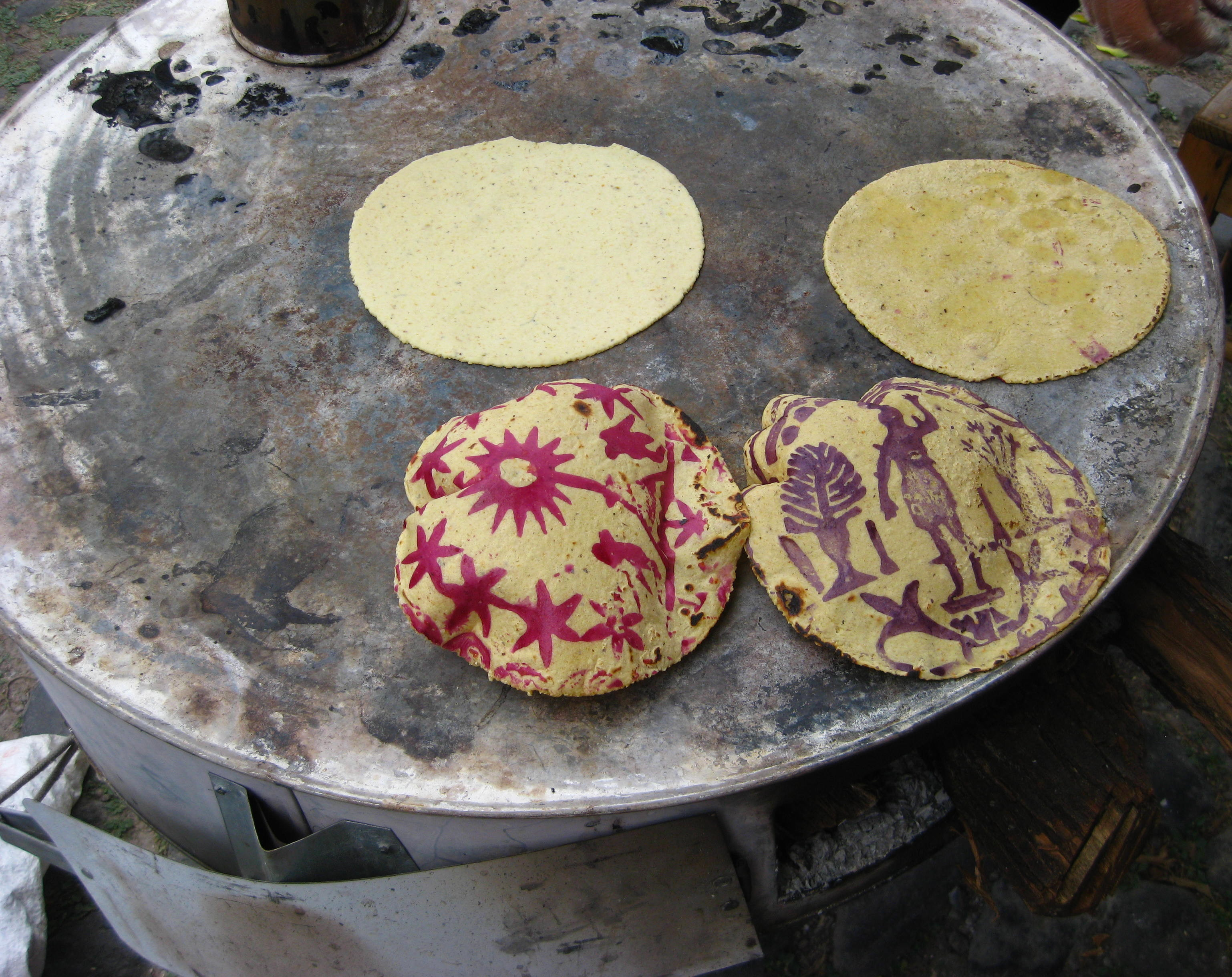 Criollo corn tortillas on the comal, with traditional designs of beet and fruit juices